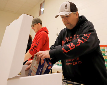 Salvation Army volunteer Rick Pander fills a box of food Friday preparing for the organization's Christmas food distribution. Pander and members of the Butler area Alliance of Bikers Aimed Toward Education (A.B.A.T.E.) set up an assembly-line-style food packaging system to fill the organization's need. Seb Foltz/Butler Eagle 12/18/20