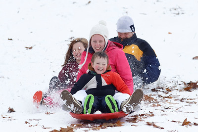 Miles Hall, 4 and his mother Charlene race against his dad Thorton and sister Della, 9, on the the sled hill at Moraine State Park's South shore Thursday. Seb Foltz/Butler Eagle