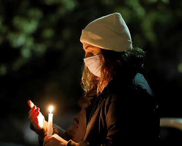 Samantha Roth of Butler tends to her candle at Tuesday night's prayer vigil outside of Butler Memorial Hospital. Seb Foltz/Butler Eagle 12/22/20