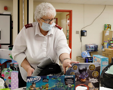 Butler Salvation Army captain Darlene Means (right) picks out gifts for a family in need as part of the organization's Christmas Toy Drive Friday. Seb Foltz/Butler Eagle 12/19/20