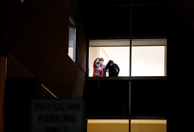 Hospital staff look on from a window during Tuesday night's prayer vigil outside of Butler Memorial Hospital. Seb Foltz/Butler Eagle 12/22/20