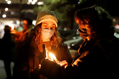 Samantha Roth of Butler helps her mother Arlene Roth relight her candle at Tuesday night's prayer vigil outside of Butler Memorial Hospital. Seb Foltz/Butler Eagle 12/22/20