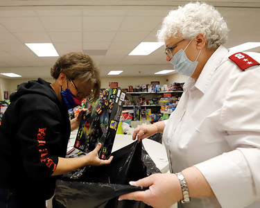Butler Salvation Army captain Darlene Means (right) and Amy Tebay pack gifts for a toy drive family Friday. Seb Foltz/Butler Eagle 12/18/20