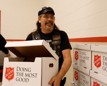 EDITORS NOTE: PHOTO FOCUS A LITTLE SOFT RUN SMALLER OR AS SECONDARY: Salvation Army volunteer Eric Mershimer stacks boxes of food Friday preparing for the organization's Christmas food distribution. Mershimer and members of the Butler-area Alliance of Bikers Aimed Toward Education (A.B.A.T.E.) set up an assembly-line-style food packaging system to fill the organization's need. Seb Foltz/Butler Eagle 12/18/20