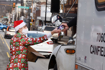Ian Robb of Cabot, a senior at Knoch High School, helped out his dad, Mike Robb, ceo and president of the Center for Community Resources, hand out cookies on Main Street in Butler Wednesday, December 23, 2020.