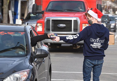 Josh Riesmeyer, a fiscal technician at Alliance for Nonprofit Resources, helped the Center for Community Resources hand out cookies along Main Street in Butler Wednesday, December 23, 2020. Harold Aughton/Butler Eagle.