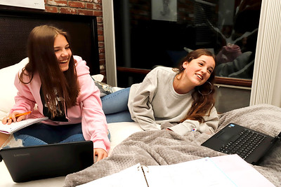 Tayla Fullerton,15,(left) and Fullerton family exchange student Blanca Arenas Giribet, 16, laugh with family demonstrating how they study. The two are doing online schooling at Seneca Valley High School during the pandemic. Seb Foltz/ButlerEagle 12/18/20