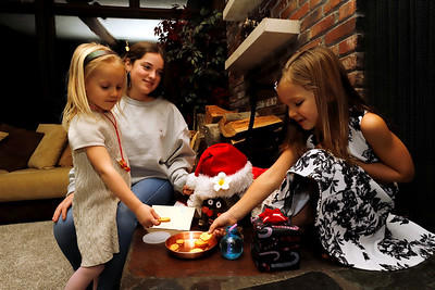 Scotlyn Fullerton, 5, (left)and her sister Lochlan, 6, leave a snack for ___  , a Spanish Christmas tradition they learned form the family's exchange student Blanca Arenas Giribet, 16 (center). Seb Foltz/Butler Eagle 12/18/20