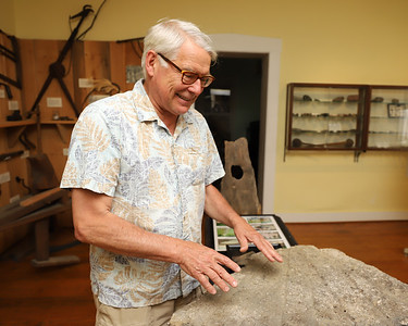 Historic Harmony president Rodney Gasch explains features of an old mill stone from the old Harmony area mill. Seb Foltz/Butler Eagle  (June 2020)