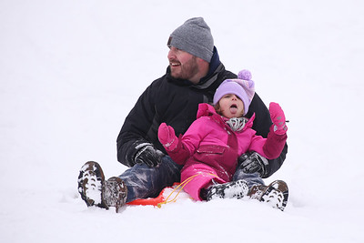 Ava Beatty, 4, of Cranberry trys to catch some snow after coming to a stop at the bottom of one of the sledding hills at North Boundary Park with her father Ken Beatty Saturday. With temperatures in the high teens and low 20s area residents still took advantage of fresh snow the day after Christmas. Seb Foltz/Butler Eagle 12/26/20