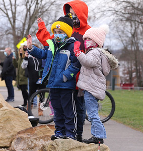 Tenley Gussey (right), 4, and her brothers Lucca, 5, and Christopher, 9, (back) wave to Santa in Cranberry Community Park during Saturday's Cranberry Township Santa parade. Emergency responders passed through Cranberry's major parks with Santa before concluding at the township municipal building. Seb Foltz/Butler Eagle 12/05/20