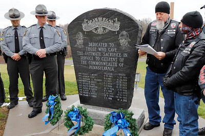 Mark 'Detune' Hensel of the Enforcers Motorcycle Club honors fallen state troopers during a ceremonial wreath laying with club mortorcycle members and officers from the Pennsylvania State Police at the Butler barracks Saturday. Seb Foltz/Butler Eagle