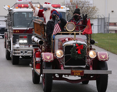Bill Ahlgren (right) and Jim Cole of the Cranberry Township Fire Department drive Santa through Cranberry Community Park Saturday in the company's 1928 Pirsch fire truck. The procession of fire trucks, police and EMT vehichles made it's way through the townships largest parks before concluding at the municipal building.  Seb Foltz/Butler Eagle 12/05/20