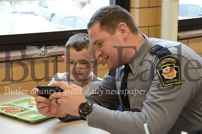 Trooper Cody Spangler shows first grader Jonah Toogood some pictures of a helicopter he is trained to pilot at Butler Catholic School.Butler Catholic School had over a dozen state troopers for lunch Jan. 29 during Catholic Schools Week. 2020