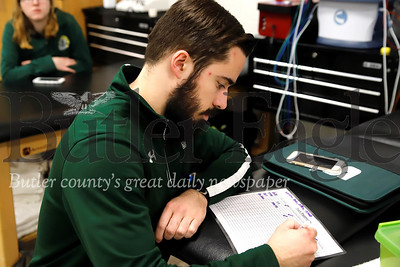 Slippery Rock University student trainer Matt Zittle looks over athlete charts to assist with training and rehabilitation plans. Seb Foltz/Butler Eagle