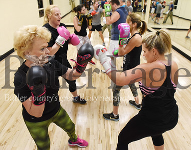 Harold Aughton/Butler Eagle: Doris Burd, left, of Harmony dukes it out with her daughter Nicole Reep during a recent couples boxing class at the Cranberry YMCA.