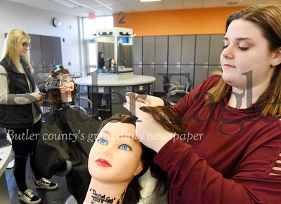 Harold Aughton/Butler Eagle: Brianna Wells (right) , 12th grade, practices her braiding technique as Maria Pascazi,12th grade, works on her curling skills at the Butler County Vo-tech.