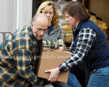 Harold Aughton/Butler Eagle: Janine Kennedy, left, of the Alliance for Nonprofit Resources gives Tom Rea of Chicora a helping hand as they load his truck with food to be delivered to the Petrolia Valley Food Cupboard.