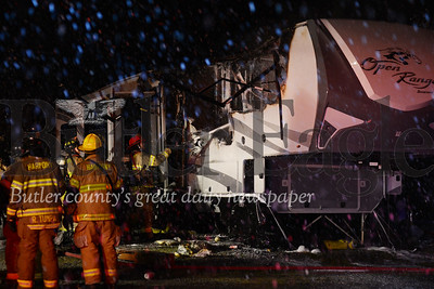 A firefighter from Harmony Volunteer Fire Company sprays down a 40-foot-long camper that caught fire twice Wednesday in Indian Brave Campground, Jackson Township. Alex J. Weidenhof/Butler Eagle