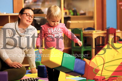 Corbin Bargo, 2, of Meridian knocks over a block stack she build with her mom Bryn Bargo in the kids play area at the Butler Library Wednesday. Seb Foltz/Butler Eagle