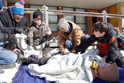 Carson Stewart(center) plays victim in a simulated first aid scenario while Kaden Crocker(right) Brady Stewart, Gabe Oddo assess injuries with one of the troop's leaders, Duane Jackson (left), and other members of Boy Scout Toop 19 of Meridian. Boy Scouts  from accross the region gathered at camp Buccoco Saturday near Slippery Rock to compete in the annual Boy Scout Klondike Derby. The event includes competitions in a various winter outdoor scenerios  with the wining troop being awarded the scouts' North Pole trophy. Seb Foltz/Butler Eagle