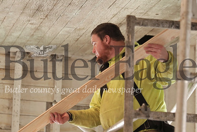 Lee Little lifts the first plank of wood for what will be the restored ceiling of the Foltz School House off of Route 8 South of Slippery Rock. Volunteers from the Eastern Atlantic States Council of Carpenters will be spending the next few weekends helping restore the building. Seb Foltz/Butler Eagle 02/15/20