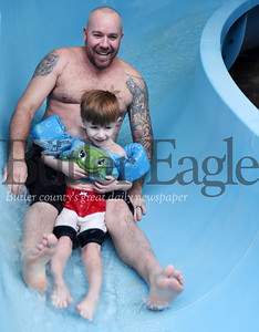 Harold Aughton/Butler Eagle: Presley, 4, and his dad, Jason Rudge take a ride on the slide during the Autism Society swim event at Conley's Resort Monday, February 17, 2018.