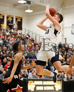 Knoch senior Jake Schiedt (33) extends for a shot in the key against New Castle's Michael Graham (1). New Castle topped the Knights 56-55 in Saturday's WPIAL playoff at North Allegheny.  Seb Foltz/Butler Eagle