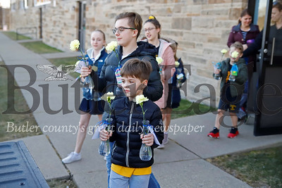 Matthew Dudley, 6, Jacob Hauser, 12, and other students from Butler Catholic School carry out donated flowers, leftover form Butler Catholic School's Purse Bash Fundraiser, for delivery to residents at area senior care facilities. Students from Butler Catholic made cards and helped deliver the left over flowers Saturday following the previous night's fundraiser. Seb Foltz/Butler Eagle