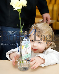 Benjamin Hauser, 2, places a flower on a table at Sunnyview Nursing and Rehabilitation Center. Seb Foltz/Butler Eagle