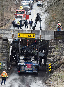 Workers review the damage after a car carrier became stuck as it attempted to travel under the railroad bridge on McCalmont Road in Penn Township, Monday, February 25, 2020.