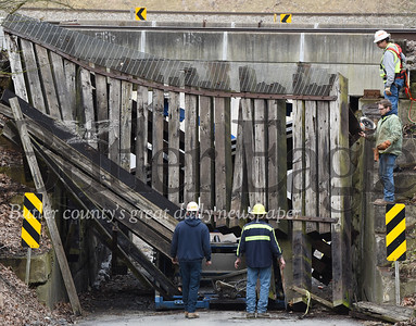 Harold Aughton/Butler Eagle: Workers review the damage after a car carrier became stuck as it attempted to travel under the railroad bridge on McCalmont Road in Penn Township, Monday, February 25, 2020.