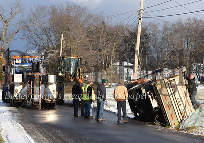 Harold Aughton/Butler Eagle: A towtruck driver attaches a chain to a Jefferson Twp. municipality truck after it flipped on its side while salting the road Wednesday, January 8, 2020.