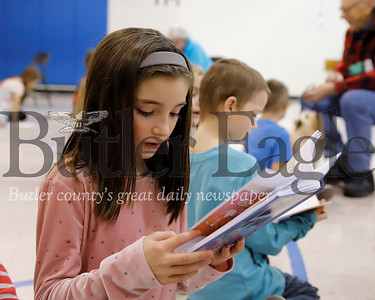 McQuistion Elementary third grader Raeleigh Niemeyer reads to one of the Butler Dog Training Association's therapy dogs during the school's read to dogs program Friday. Seb Foltz/Butler Eagle
