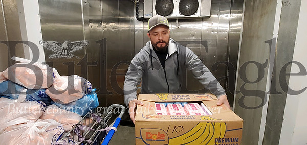 Volunteer Julian Trigueros of Butler packs some boxes full of food into the cooler at St. Vincent DePaul on Friday. Nathan Bottiger/Butler Eagle