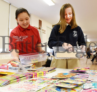 Harold Aughton/Butler Eagle: Holy Sepcular sixth graders Kelly Andrews, left, and Sienna Waldenville recently filled containers for Jared's Box, a service project as part of Catholic Schools week.