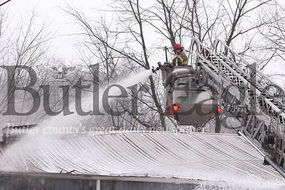 Cranberry firefighters dowse remaining hot spots on the structure fire that closed north and southbound lanes of route 19 north of Cranberry Tuesday. Seb Foltz/Butler Eagle