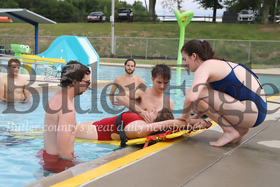 Celia Ray(right) and Andy Kamis place Madison Rees on a backboard during lifeguard training with instructor Zachery Hoover (center) last Friday at the Alemeda Park Pool. The pool opened to the public Wednesday. Seb Foltz/Butler Eagle 06/26/20