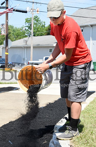 Harold Aughton/Butler Eagle: Ray Dean III distributes a bucket of mulch at the West Sunbury veterans memorial. Dean is working on his Eagle Scout project . Thursday, June 2, 2020.