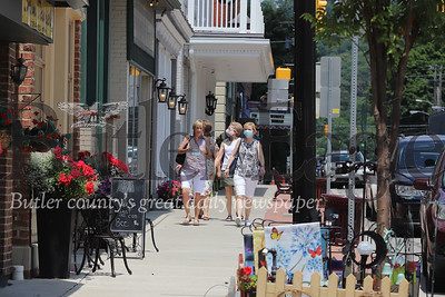People walk beside Main Street businesses in downtown Zelienople Wednesday. Borough council on Monday approved a request by the Zelienople Business Association to allow businesses to sell goods outside their shops or bring in vendors who may attract customers to the store. Seb Foltz/butler Eagle July 2, 2020
