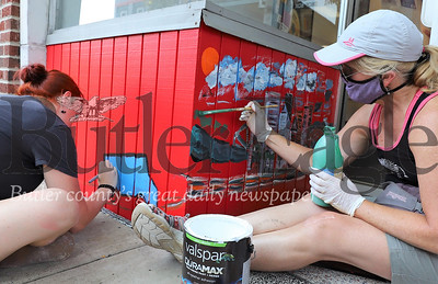 Kristen Reed (left) and Amy McKay from the Butler Art Center Paint a mural on the Sir Speedy storefront on Main St.  (Details in today's story, partnership with city?) Seb Foltz/Butler Eagle