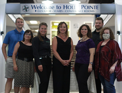 BIZMATTERS PHOTOSLUG: 0801_BIZMATTERS_HOLLY POINTE REMODEL - Jordan Grady, Stephanie Steiger, Tara Levere, Trisha Pritchard, Cheri Readie, Logan Maxwell, Gael Gilliland, stand in front of the new signage in the modernized grand entryway of the Holly Pointe Building on Main Street in Butler. The building was unveiled on July 9,2020 at a VIP Mixer that ran from 4 p.m. to 6 p.m. Readie, took the opportunity that the coronavirus presented of restricted traffic into the building to make a highly anticipated update to the public spaces of the Holly Pointe. It was a rebranding that included new paint, a new color scheme, upcycled materials from the 80's that create a sleek modern new look.With the help the Paycheck Protection Program, Readie used the funds to help keep her staff employed during the 5 week facelift. Readie says approximately 50 people attend the mixer which included handmade sushi by her husband, Shawn Readie, professional headshots sponsored by Connectwork on Main, one of the tenants in the Holly Pointe, and tours showcasing all the renovations and a few tenants in the building such as Dress for Success.  Photo - Lauryn Halahurich/Butler Eagle