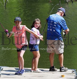 Harold Aughton/Butler Eagle: Mackenzie Peck, 10, leaps into action to help her grandfather, Richard Sittler, find a net after her sister, Madison, 7, caught a small mouth bass Monday afternoon at Glade Run Lake