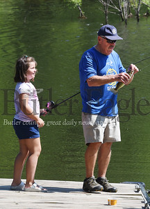 Harold Aughton/Butler Eagle: Madison Peck, 7, looks on as her grandfather Richard Sittler, removes the hook from the small mouth bass she caught on the first cast Monday afternoon at Glade Run Lake.