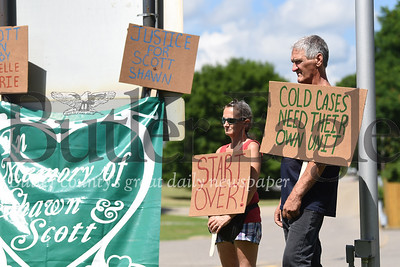 Ailvie Rausch, front, stands with Randy Rausch, both of Moon, to look at a sign brought by a family friend to the rally at the Butler State Police Barracks on Friday. The rally was held to support public awareness of the 18-year-old cold case involving Scott Fosnaught, Ailvie's son, and Shawn Baur, two 15-year-olds who died under mysterious circumstances in 2002 in Forward Township.Photo by Lauryn Halahurich/Butler Eagle