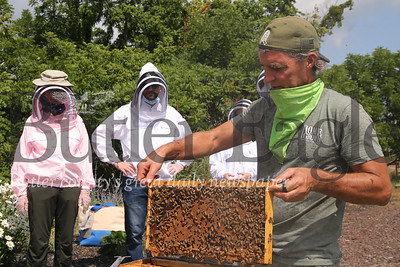 Jeff Shaw of Burgh Bees shows guests a beehive frame during a program at the Cranberry Highlands Community Apiary Sunday. Seb Foltz/Butler Eagle 07/19/20