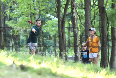Tim Wharton throws a disc toward the eighth basket at North Boundary Park's disc golf course in Cranberry Wednesday with his wife Erin and two sons Abe, 6, and Eli, 8(not pictured). Seb Foltz/Butler Eagle 07/15/20