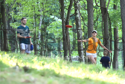 Erin Wharton throws a disc toward the eighth basket at North Boundary Park's disc golf course in Cranberry Wednesday with her husband Tim and two sons Abe, 6, and Eli, 8(not pictured). Seb Foltz/Butler Eagle 07/15/20