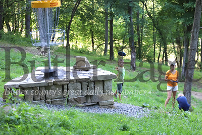 Eli Wharton, 8, throws a disc at the seventh pin at North Boundary Park's disc golf course Wednesday with his mother Erin Wharton, brother Gabe, 6, and father Tim(not pictured). Seb Foltz/ButlerEagle 07/15/20
