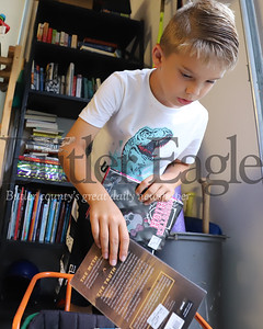 Parker Knobeloch sorts through donated books for his new library box. Seb Foltz/Butler Eagle